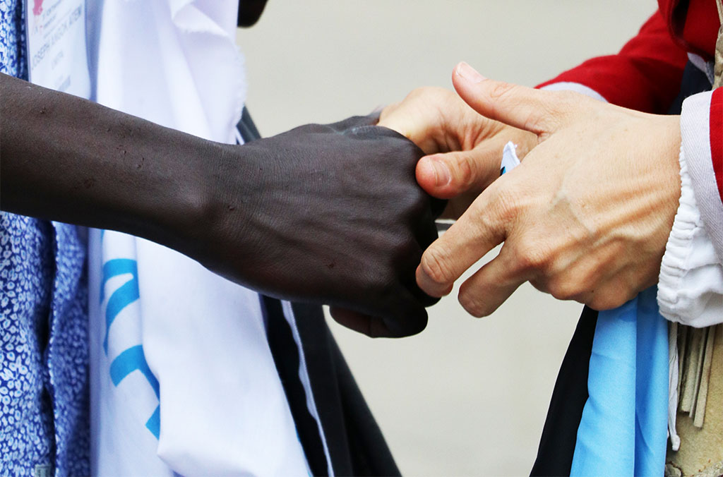 Midwives from South Sudan and Canada hold hands